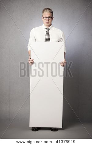 Surprised sad businessman holding white empty vertical billboard with space for text isolated on grey background.