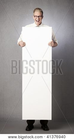 Happy laughing businessman holding white blank vertical billboard with space for text isolated on grey background.