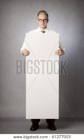 Confident businessman holding white empty vertical panel with space for text isolated on grey background.