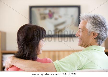 Paare beobachten Fernsehen lächelnd