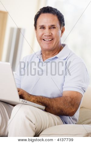 Man In Living Room With Laptop Smiling