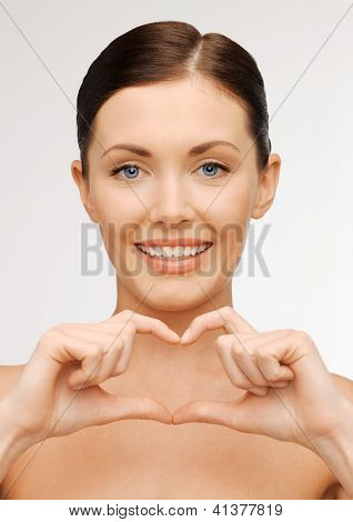 bright picture of beautiful woman showing heart shape