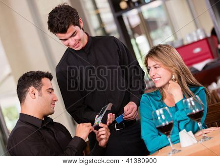Man paying by credit card at a restaurant