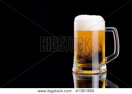 Mug Fresh Beer With Cap Of Foam On A Black Background