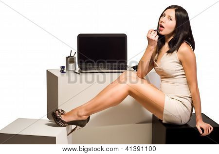 Beautiful young girl paints her lips with lipstick sitting at the computer in the office