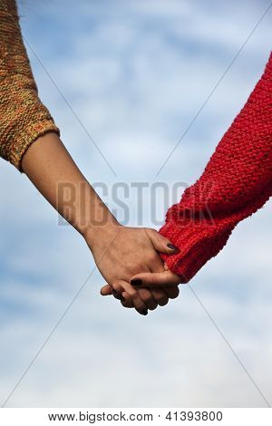 Couple holding hands over blue background