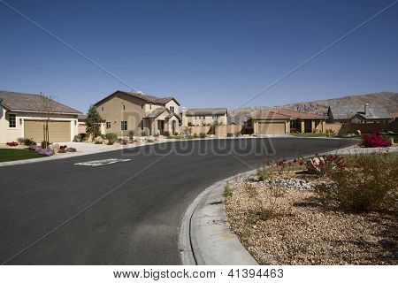 Empty curved road in front of a raw of houses