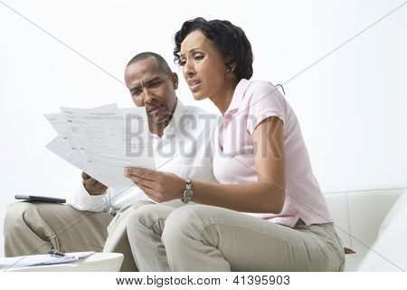 Worried African American couple looking at their bills