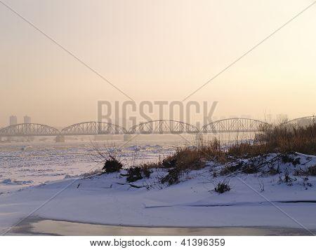 Winter brige in fog. sunset