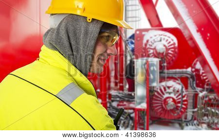 Shipping engineer on a cold winter day, on the snowy bridge of an offshore support vessel, wearing a hoodie and safety gear, such as a hard hat, goggles and reflective coat