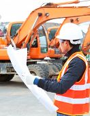 stock photo of heavy equipment operator  - road construction worker front of heavy equipment - JPG