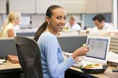 pic of african american woman  - Portrait of business woman in busy office eating lunch - JPG