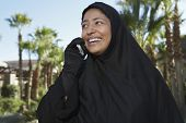 stock photo of burka  - Happy Indian woman in burka communicating on mobile phone - JPG