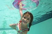 Portrait of a happy girl swimming underwater while holding inflatable ring