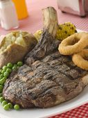Ribeye Steak On The Bone With Baked Potato Peas Onion Rings And Corn