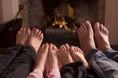 foto of happy family  - Woman sat in front of fire with mug in hand in wintertime - JPG