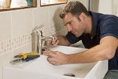stock photo of plumber  - Plumber working on sink - JPG