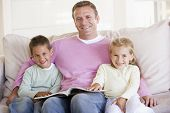 picture of father child  - Man with children reading book on sofa at home - JPG
