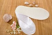 foto of spank  - Spa or hotel flip flops on a bamboo mat - JPG