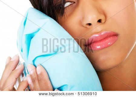 Woman pressing her bruised cheek with a painful expression as if she's having a terrible tooth ache.