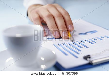Man Holding A Pencil Working On A Graph