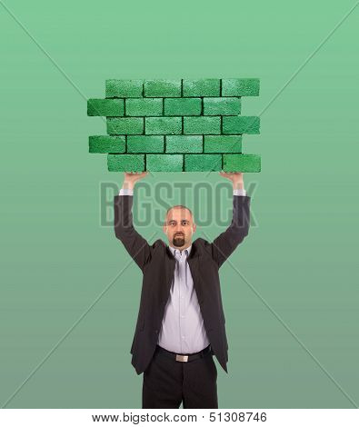 Businessman Holding A Large Piece Of A Brick Wall