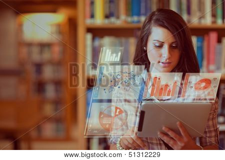 Pretty student working on her futuristic tablet pc in a library
