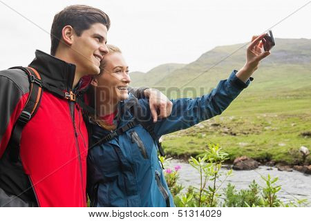 Athletic couple on a hike taking a selfie in the countryside