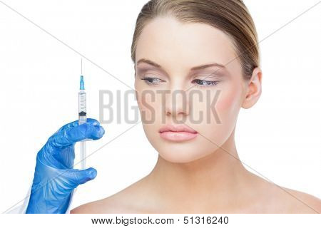 Content beautiful blonde on white background holding surgical needle