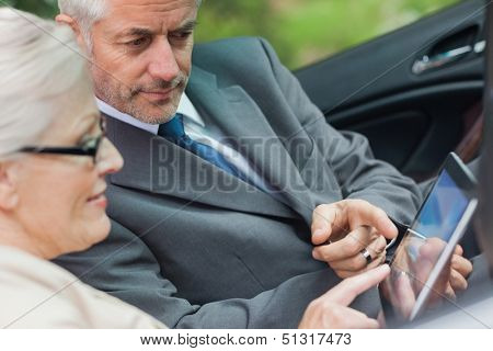 Partners working together on tablet in classy convertible on a bright day