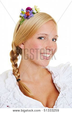 Blonde smiling woman with flowers in her hair and a french plait