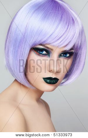 Portrait of young beautiful woman with colorful fancy make-up and violet wig