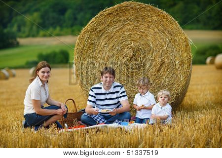 Happy Family Of Four Picnicking On Yellow Hay Field In Summer.