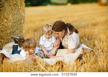Young Mother And Two Little Toddler Boys  On Yellow Hay Field