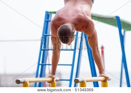 Sportsman Exercising On Bars Outdoors