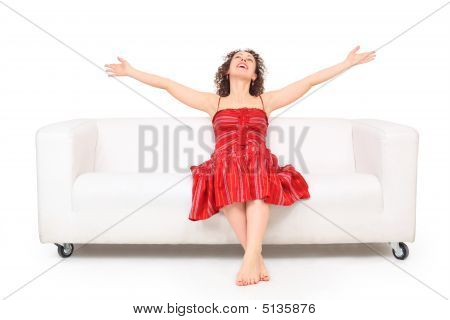 Young Beautiful Barefooted Woman In Red Dress Sits On White Leat