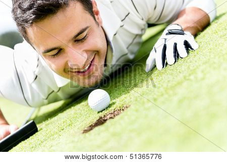 Golf player cheating by blowing the ball into a hole