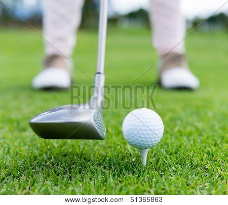 Golf player at the tee box hitting ball