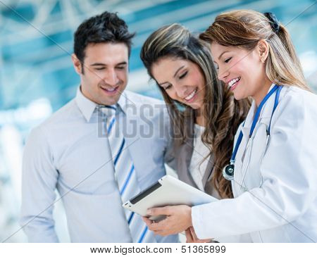Family doctor with a happy couple at the hospital
