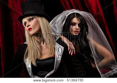 Halloween concept: sexy ladies vampire over red curtain