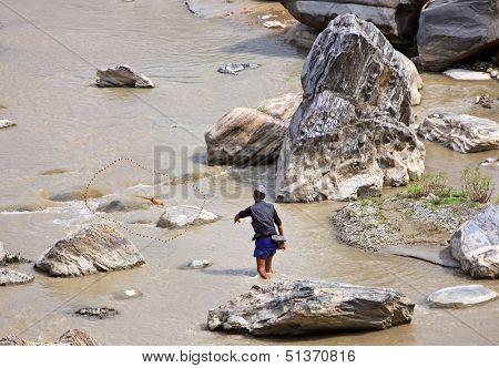 SALLAGHARI, NEPAL - APRIL 4: Portrait of unidentified Nepalese fisherman fishing on the bank of the river with traditional handmade fishing net April 4, 2009 in Sallaghari Village, Kathmandu, Nepal.