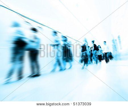 Motion blurred people walking at subway station.