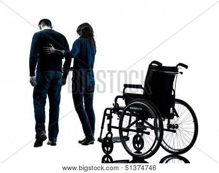 one  man with woman  walking away from  wheelchair  in silhouette studio  on white background