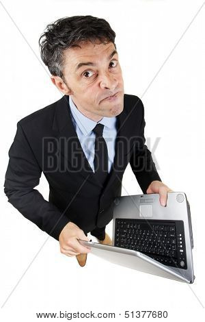 Pugnacious businessman holding a laptop computer in his hands standing looking up at the camera with a determined dogmatic expression, isolated on white