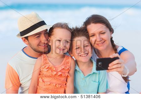Beautiful family at beach making a self portrait with a mobile phone
