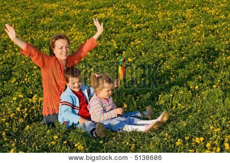 Woman With Kids On The Spring Field Full Of Dandelions