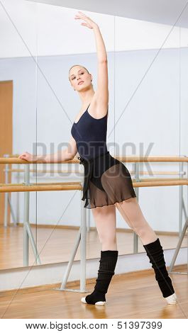 Wearing leotard and warmers ballet dancer dances near barre and mirrors in dancing hall