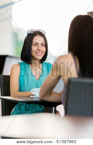 Girl wearing blue dress and sunglasses sits at the table of the cafeteria and talks with friend