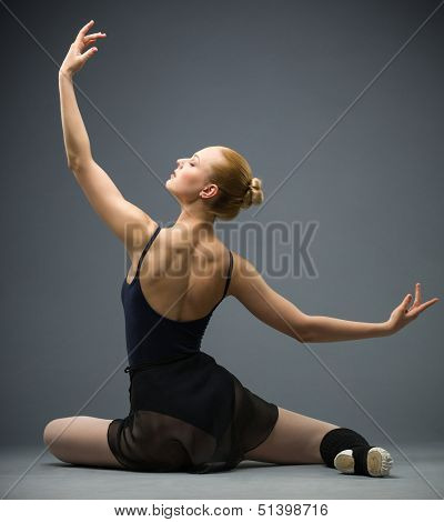 Backview of dancing on the floor ballerina with hands up, isolated on white background on grey. Concept of elegant art and sportive hobby