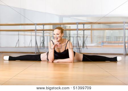 Ballerina does the splits sitting on the floor in the studio with barre and mirrors